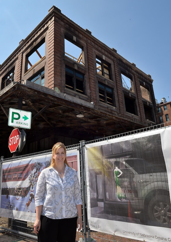 Lisa Gill, with the 55th Force Support Squadron, stands next to her banner art that surround the Mercer Building in Omaha's Old Market, May 5, 2016.  Lisa was one of two artists from Offutt Air Force Base selected to have their work displayed on the construction fence that surrounds the downtown renovation of the Mercer Building after a fire destroyed much of the century-old building.  (U.S. Air Force photo by Josh Plueger/Released)