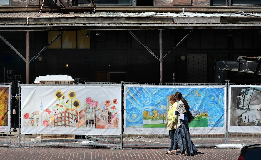 Old Market pedestrians walk by the Old Market Business Association's beautification project on Howard Street in downtown Omaha, Neb., May 5, 2016.  The fence that runs along the corner of Howard and 11th Street surrounds the construction site of the Mercer Building which almost burned down in January.  The fence displays 37, selected pieces of art from Omaha-area artists to help beautify the intersection during the renovation.  (U.S. Air Force photo by Josh Plueger/Released)