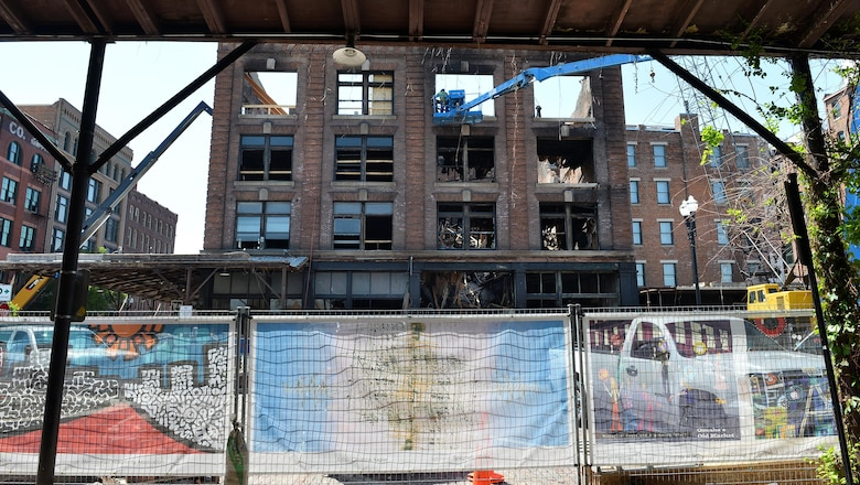 Banners, displaying Omaha-area artists' work, hang along a barrier fence that encircles the renovation efforts of the Old Market Mercer Building in downtown Omaha, Neb., May 5, 2016.  The historic building almost completely burned to the ground from a gas fire in January.  The banners are part of the Old Market Business Association's beautification project.  (U.S. Air Force photo by Josh Plueger/Released)