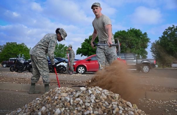 1st Lt. Lauren Lyons, 27th Special Operations Force Support Squadron Readiness and Plans chief, works on a landscaping project with another Air outside Building 600 as part of Wing Beautification Day May 13, 2016, at Cannon Air Force Base, N.M. From maintenance to medical, flyers to finance, members of the 27th SOW took time out of their day to clean-up the Cannon Community. (U.S. Air Force photo/Staff Sgt. Alexx Pons)