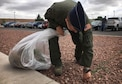 1st Lt. Malcolm Strong, 3rd Special Operations Squadron pilot, pulls out weeds outside Building 848 as part of Wing Beautification Day May 13, 2016, at Cannon Air Force Base, N.M. From maintenance to medical, flyers to finance, members of the 27th SOW took time out of their day to clean-up the Cannon Community. (U.S. Air Force photo/Staff Sgt. Alexx Pons)