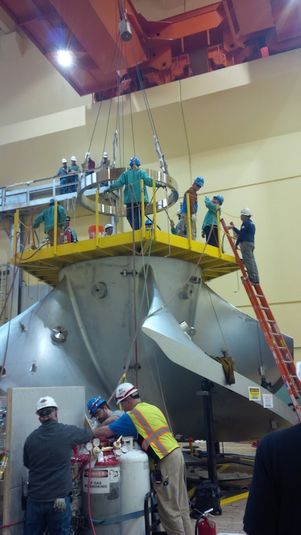 Workers assembling the new high-tech replacement turbine for Ice Harbor's hydroelectric generator Unit-2 apply heat to expand a metal ring that will lock together the turbine segments from the inside of its hub as the ring cools and shrinks back to normal size.