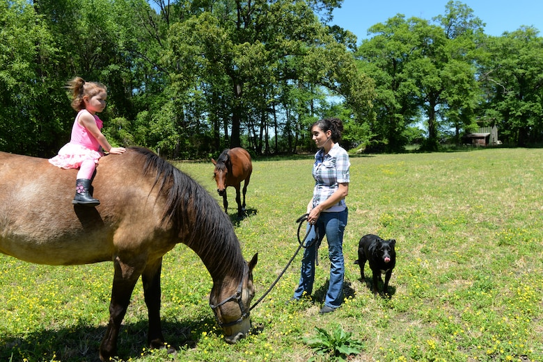 Staff Sgt. Katrina Rubisch, 4th Equipment Maintenance Squadron aircraft armament systems technician, socializes with her child and horses, March 24, 2016, in Goldsboro, North Carolina. Rubisch often brings her child to the stables to share her love of horses with her child. (U.S. Air Force photo by Airman 1st Class Ashley Williamson/Released)