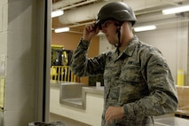 """U.S. Air Force Airman Justin Hurd, 20th Component Maintenance Squadron aerospace propulsion apprentice, tries on a helmet for size at Shaw Air Force Base, S.C., May 10, 2016. The individual protective equipment shop distributes and maintains more than 136,000 pieces of equipment including mission-oriented protective posture gear, gas masks and sleeping bags. During the """"thousand-year flood"""" October 2015, IPE loaned more than 70 sleeping bags to local shelters. (U.S. Air Force photo by Airman 1st Class Destinee Dougherty)"""