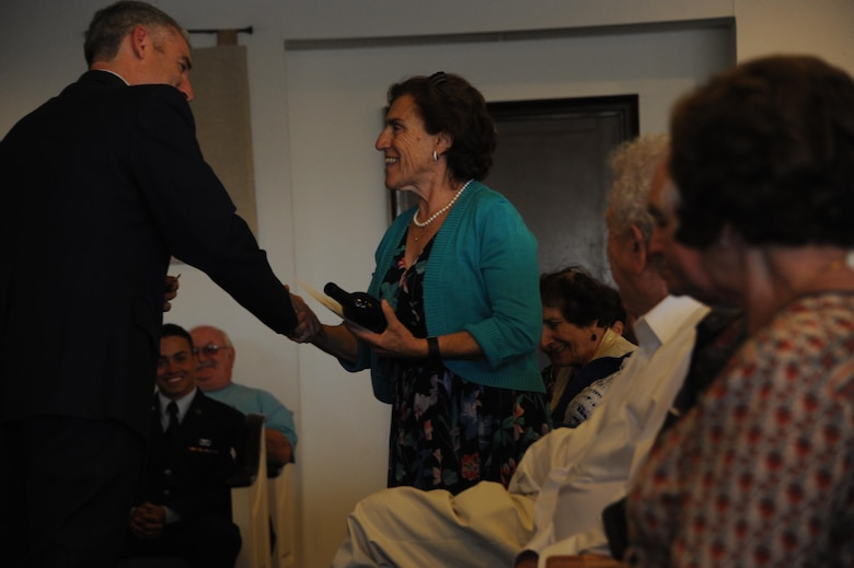 Theresa Dulgov, Holocaust survivor, is presented with a memento of appreciation from Col. Steven Renner, 355th Fighter Wing vice commander, during the Holocaust Day of Remembrance at Davis-Monthan Air Force Base, Ariz., May 9, 2016. Eight Holocaust survivors spoke to Airmen and family members about their personal accounts of survival during the holocaust. (U.S. Air Force photo by Airman Nathan H. Barbour)