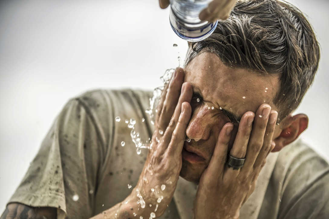 Air Force Senior Airman Jacob Nevills washes the concrete from his face after helping fill a footer at Bagram Airfield, Afghanistan, May 3, 2016. Nevills is assigned to the 455th Expeditionary Civil Engineer Squadron, whose members dug eight trenches to house eight footers for placing four relocatable buildings. Air Force photo by Senior Airman Justyn M. Freeman