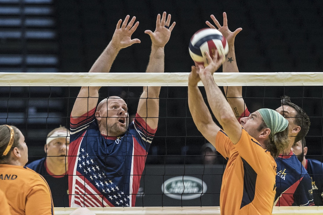 Navy veteran Brett Parks, left, and Army veteran Nicholas Titman attempt to block a shot in a sitting volleyball game against Denmark at the 2016 Invictus Games in Orlando, Fla., May 11, 2016. DoD photo by Roger Wollenberg