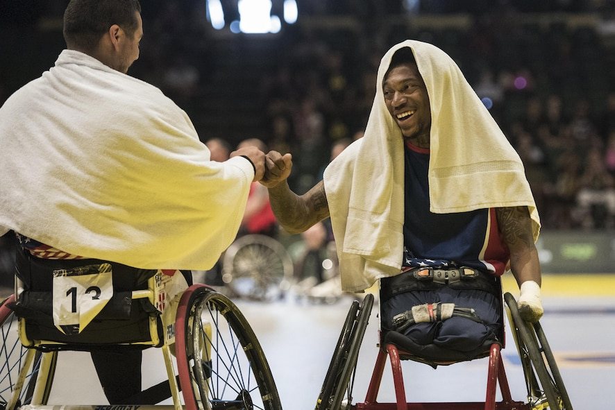 Marine Corps veterans Eric Rodriguez, left, and Anthony McDaniel fist bump as the U.S. team takes a timeout against the British team during the gold medal wheelchair basketball competition,