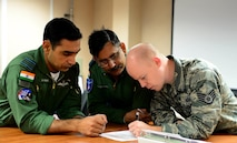 An operations airman helps Indian Air Force pilots complete a mission brief prior to a scheduled sortie, here, May 12, 2016.(U.S. Air Force photo by Airman 1st Class Cassandra Whitman)