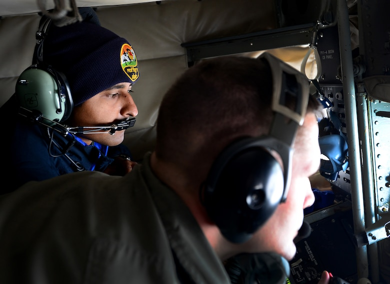 U.S. Air Force Senior Master Sgt. Doug Palmisano, a boom operator with the 909th Air Refueling squadron, Kadena Air Base, Japan, refuels an aircraft while an Indian Air Force (IAF) airman watches during an incentive flight May 10, 2016, over the skies of Alaska. Ten IAF airmen were able to view U.S. Air Force F-16 Fighting Falcon aircraft being refueled. (U.S. Air Force photo by Airman 1st Class Cassandra Whitman)