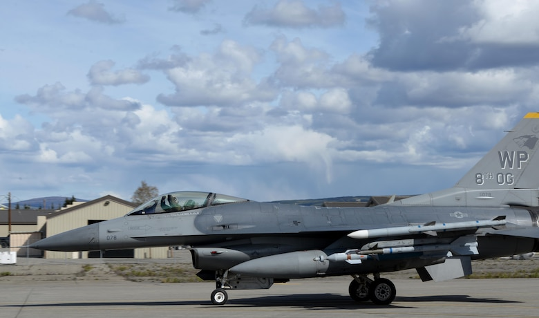 A U.S. Air Force F-16 Fighting Falcon pilot assigned to the 80th Fighter Squadron out of Kunsan Air Base, Republic of Korea, taxis down the Eielson Air Force Base, Alaska, flight line in a jet painted with the 8th Operations Group markings, May 4, 2016, in preparation for a RED FLAG-Alaska (RF-A) 16-1 afternoon mission. The Joint Pacific Alaska Range Complex provides units like the Wolf Pack access to a realistic training environment and allows commanders to train for full spectrum engagements ranging from individual skills to complex, large-scale joint engagements. (U.S. Air Force photo by Master Sgt. Karen J. Tomasik/Released)