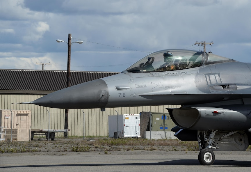 A U.S. Air Force F-16 Fighting Falcon assigned to the 80th Fighter Squadron out of Kunsan Air Base, Republic of Korea, looks on as he taxis along the Eielson Air Force Base, Alaska, flight line May 4, 2016, in preparation for a RED FLAG-Alaska (RF-A) 16-1 afternoon mission. RF-A is a series of Pacific Air Forces commander-directed field training exercises for U.S. and partner nation forces, enabling joint and international units to sharpen their combat skills by flying simulated combat sorties in a realistic threat environment inside the Joint Pacific Alaska Range Complex, the largest instrumented air, ground and electronic combat training range in the world. (U.S. Air Force photo by Master Sgt. Karen J. Tomasik/Released)