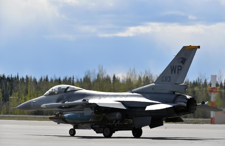 A U.S. Air Force F-16 Fighting Falcon pilot assigned to the 80th Fighter Squadron out of Kunsan Air Base, Republic of Korea, taxis down the Eielson Air Force Base, Alaska, flight line May 5, 2016, in preparation for a RED FLAG-Alaska (RF-A) 16-1 afternoon mission. The Joint Pacific Alaska Range Complex provides units like the Wolf Pack access to a realistic training environment and allows commanders to train for full spectrum engagements ranging from individual skills to complex, large-scale joint engagements. (U.S. Air Force photo by Master Sgt. Karen J. Tomasik/Released)
