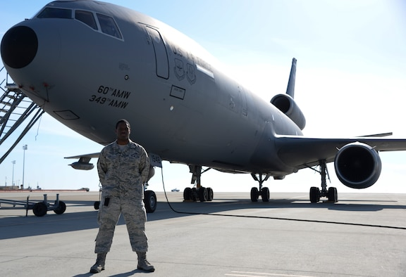 Staff Sgt. Terrell Cole, 660th Aircraft Maintenance Squadron communication/navigation mission systems craftsman, poses for a photo in front of a KC-10 Extender May 11 at Travis Air Force Base, Calif. (U.S. Air Force photo by Senior Airman Amber Carter)