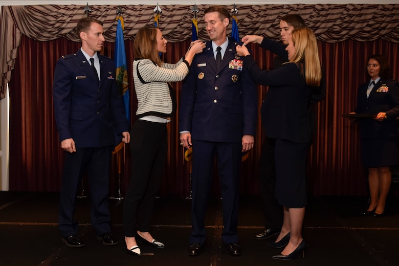 : Brig. Gen. Tom D. Miller, Air Force Sustainment Center vice commander, has his stars placed on the right side of his service jacket by his wife, Kim Miller, and son Airman Joshua Miller, and on his left side by his daughter Ashley Schultz and son-in-law, 2nd Lt. Jeff Schultz, Air Force Reserve Command, during his promotion ceremony at the Tinker Club May 10. General Miller was commissioned via the Reserve Officer Training Corps 26 years ago. (Air Force photo by Greg Davis/Released)