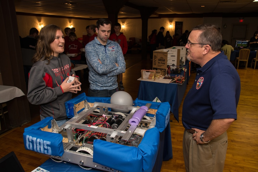 "A student from Tri Village High School discusses her STEM project with Winston ""Wink"" Bennett, technical advisor for the Warfighter Readiness Research Division in the 711th Human Performance Wing, during the Full Throttle STEM® at Eldora Day May 10 at Eldora Speedway in Rossburg, Ohio. (U.S. Air Force photo/Richard Eldridge)"