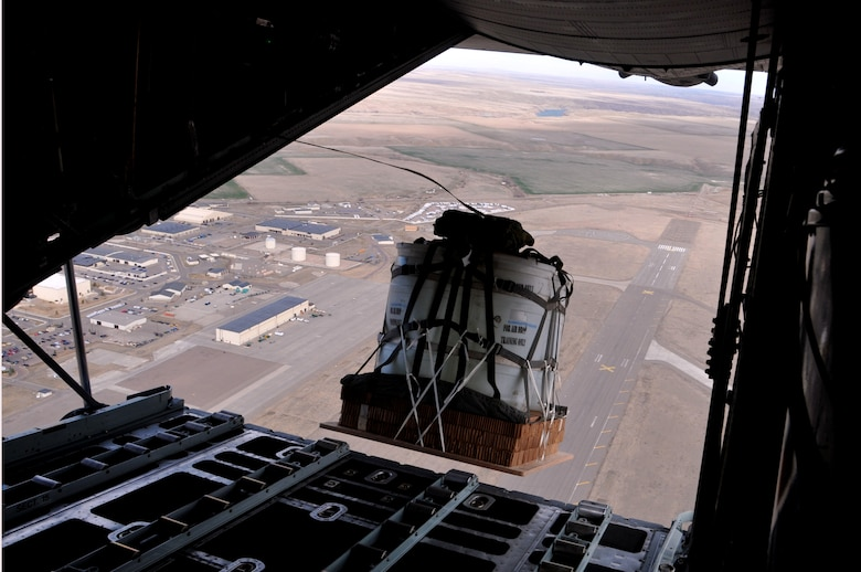 A training cargo load exits a Montana Air National Guard C-130 cargo aircraft over the drop zone Chargin' Charlie near Malmstrom Air Force Base, Mont. March 5, 2016. Each load weighs nearly 1,000 pounds and was dropped from an altitude of 1500 feet. (U.S. Air National Guard photo/Tech. Sgt. Michael Touchette)