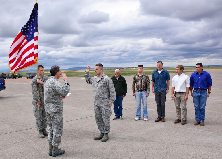 Col. Thomas Mora, 120th Airlift Wing vice commander, swears in Capt. Kevin Ochs, 219th RED HORSE engineer, on the 120th Airlift Wing flight line in front of a C-130 Hercules April 30, 2016. Ochs lead five new enlistees through the initial oath of enlistment after taking his oath. (U.S. Air National Guard photo/Senior Master Sgt. Eric Peterson)