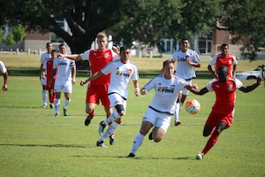 Fort Benning, Ga. - Army Capt Andrew Hyres (center with ball) drives down the field on the opening 30 seconds of the match to put Army on the board 1-0 of the consolation match of the 2016 Armed Forces Men's Soccer Championship hosted at Fort Benning, Ga from 6-14 May 2016.  Marine Corps would win the match 3-2, placing them third overall and Army in fourth.