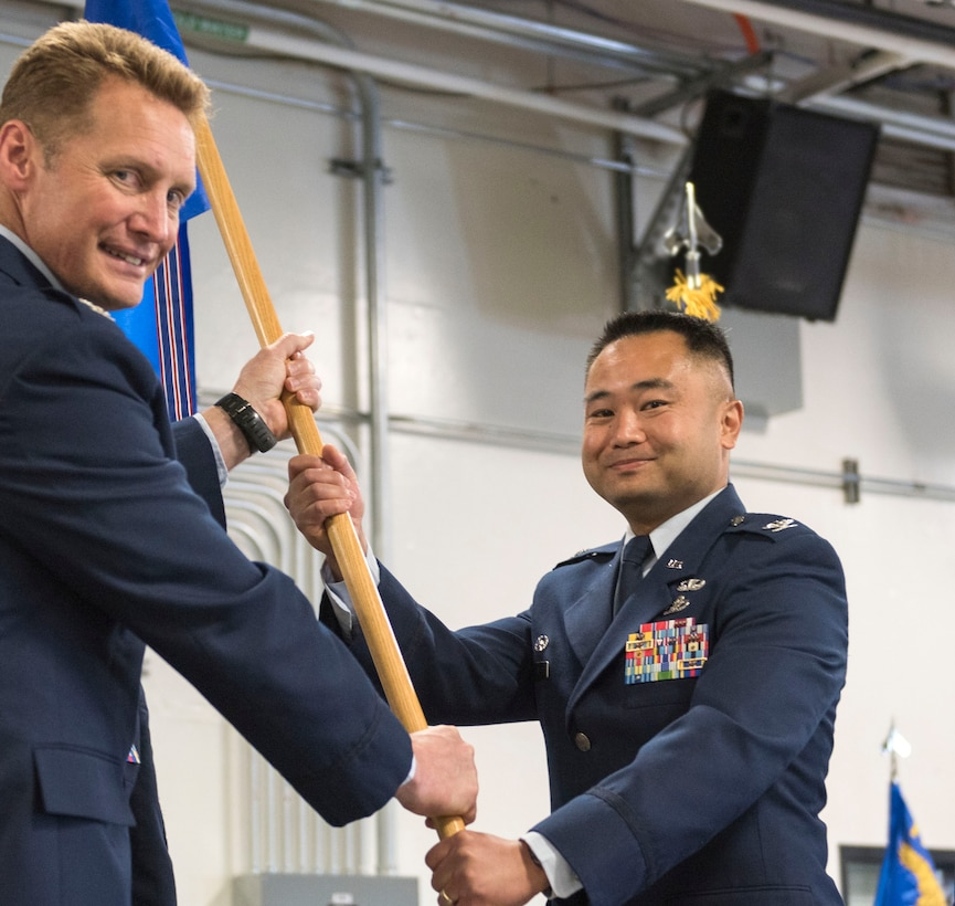 Col. Marvin T. Ee accepts the 176th Mission Support Group command flag from 176th Wing commander Col. Blake Gettys at a ceremony on Joint Base Elmendorf-Richardson. National Guard photo by Tech. Sgt. N. Alicia Halla.