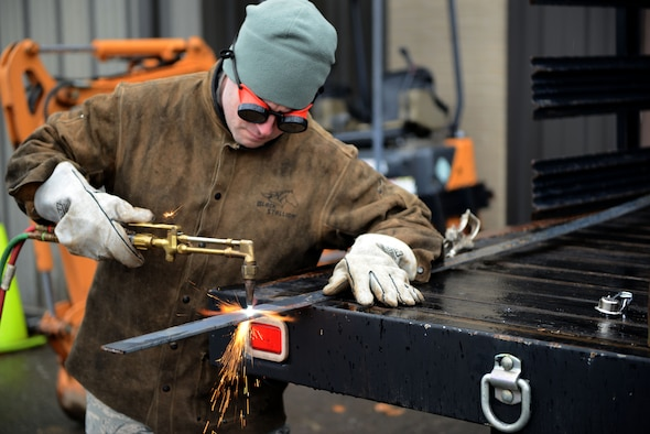 Senior Airman Eric Burton, a structural craftsman assigned to the 103rd Civil Engineer Squadron, slices through a piece of metal using an acetylene oxygen cutter on Bradley Air National Guard Base, East Granby, Conn., April 2, 2016. The metal being cut will be used to practice welding when the Flying Yankee craftsmen travel to Barnes Air National Guard base, Westfield, Mass., to sharpen their skills. (U.S. Air National Guard photo by Senior Airman Emmanuel Santiago)