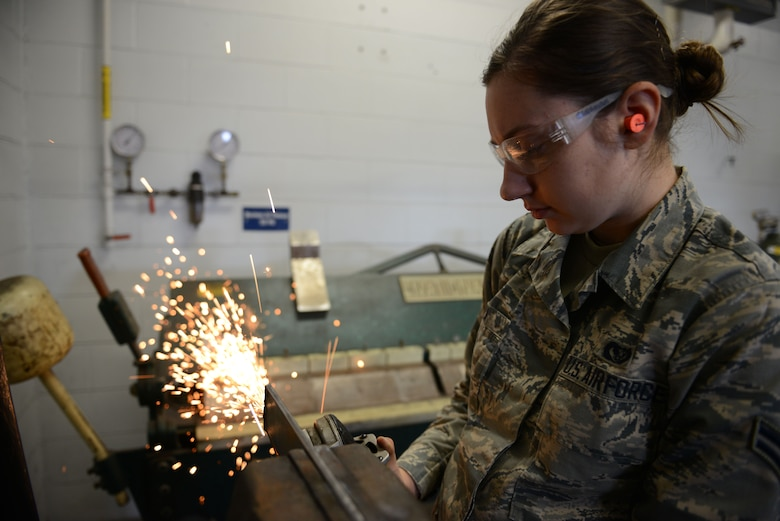 Airman 1st Class Katie Puza, a structural craftsmen assigned to the 103rd Airlift Wing, cleans a piece of metal with a grinder on Barnes Air National Guard Base, Westfield Mass., April 3, 2016. The Flying Yankees had the opportunity to use the facilities at Barnes to undergo a refresher course in welding. (U.S. Air National Guard photo by Senior Airman Emmanuel Santiago)