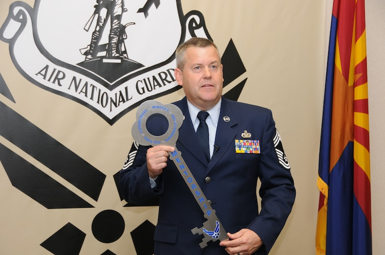 Chief Master Sgt. Bert Reid, 161st Logistics Readiness Squadron chief enlisted manager, displays a key that will be hung in the new Center for Enlisted Leadership and Learning center. The key signifies the attributes for successful mentorship: culture, commitment, mindset and relationships.