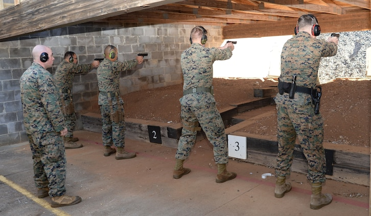 "Active-duty service members and Marine Corps police officers ""take aim"" in one of several Combat Pistol Program training courses officials host at Marine Corps Logistics Base Albany's pistol range throughout the year. As the combat marksmanship coach looked on, shooters fired live rounds at targets during their course of fire qualification. The CPP is a five-day training course held on the installation's pistol range to facilitate annual qualification requirements for service members and law enforcement personnel."