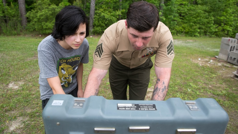 Sgt. Doug Hardy, an Explosive Ordnance Disposal technician with EOD Company, 8th Engineer Support Battalion, shows a student how to operate a robot during a robotics demonstration at Swansboro High School in Swansboro, N.C., May 10, 2016. Marines with EOD Co. demonstrated the capabilities of two robotics platforms to Swansboro High School's robotics club to help the students imagine the endless creative possibilities of robotics and engineering.