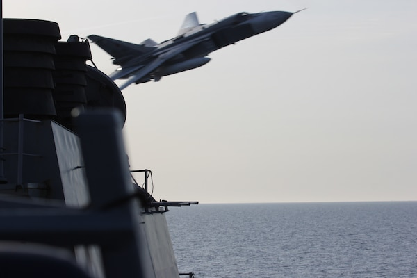 A Russian Sukhoi Su-24 attack aircraft makes a very low-altitude pass by the guided-missile destroyer USS Donald Cook in international waters in the Baltic Sea
