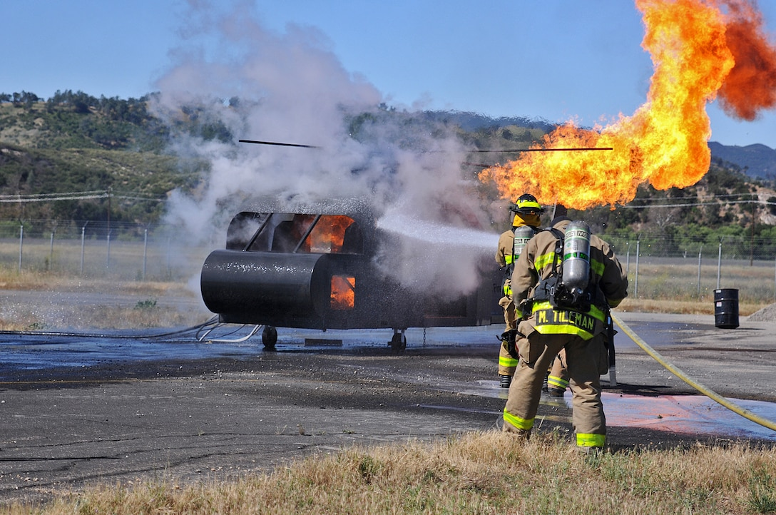JOLON, Calif. – Fire fighting Soldiers with the 614th Engineer Detachment attack a helicopter-fuselage fire during a multi-unit mass casualty exercise at Fort Hunter Liggett's Tusi Airfield, May 9. The realistic exercise was apart of the Fort's 16th Annual Warrior Exercise and the scenario encompassed a simulated helicopter crash, which had burst into flames and 32 casualties laid scattered around the helicopter.   (U.S. Army photo by Sgt. Kimberly Browne, 350th Public Affairs Detachment)