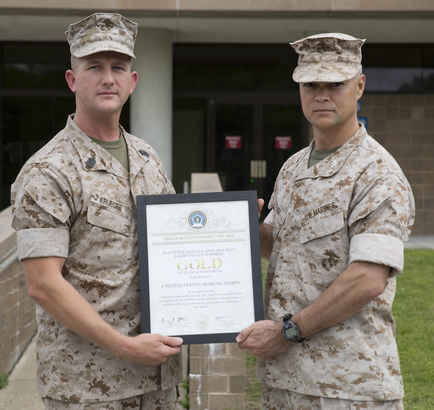 Col. John E. Walker Jr., right, Commanding Officer of Marine Corps Intelligence Schools, and Master Sgt. Eldar Krueger, MCIS S-6 Chief, display the Department of Defense Intelligence and Security Learning Enterprise Gold Level of Achievement Award for 2015. MCIS received the Gold Level award for being the top school, chosen from a field of 52 formal learning centers encompassing $2 billion in resources and assets across the Department of Defense.