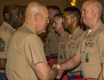Gen. Robert B. Neller, Commandant of the Marine Corps (left), congratulates Staff Sgt. Christopher Smith, the 2015 Reserve Career Planner of the Year during the Commandant of the Marine Corps Combined Awards Ceremony, held at Marine Corps Base Quantico, Va., May 11, 2016. Smith, the career planner from 3rd Air Naval Gunfire Liaison Company, Force Headquarters Group, Marine Forces Reserve, was awarded the Navy and Marine Corps Commendation Medal for his hard work and dedication. The ceremony also recognized superior recruiters, drill instructors, combat instructors, Marine security guards, career planners and Semper Fit male and female athletes of the year.