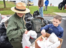Park Ranger Alicia Palmer, Baltimore District, U.S. Army Corps of Engineers, helps Grant Taylor, 8, sort through trash collected during the Raystown Lake Cleanup Day, May 7, 2016.  Taylor was among the 130 volunteers that came together to collect debris from remote areas of Raystown Lake's 110 miles of shoreline during the annual event.