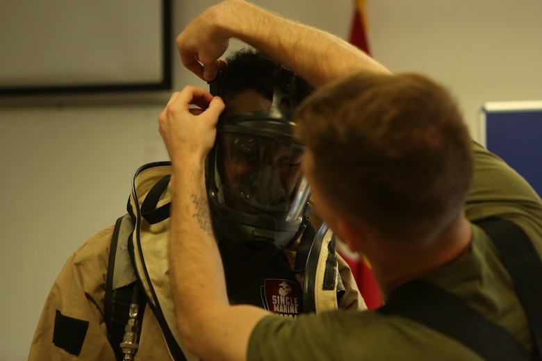 A Marine with the Chemical Biological Radiological and Nuclear (CBRN) unit receives assistance putting on a hazardous material suit during Assessment Consequence Management training aboard Marine Corps Air Station Miramar, Calif., May 6. The ACM training is conducted by CBRN once a month to maintain mission readiness. (U.S. Marine Corps photo by Pfc. Liah Kitchen/Released)