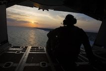An Air Commando assigned to the 15th Special Operations Squadron watches the sunset from the back of an MC-130H Combat Talon II during Exercise Emerald Warrior 16, May 12, 2016, at Hurlburt Field, Fla. Emerald Warrior is a U.S. Special Operations Command sponsored mission rehearsal exercise during which joint special operations forces train to respond to real and emerging worldwide threats. (U.S. Air Force photo by Staff Sgt. Matthew B. Fredericks)