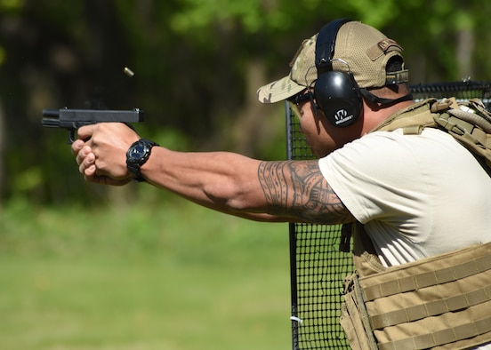 U.S. Air Force Staff Sgt. Jesse Aquino, 319th Security Forces Squadron military working dog handler, fires a pistol May 15, 2016, in East Grand Forks, Minn. Aquino was one of several Airmen to participate in a joint shooting competition held at the East Grand Forks Rod and Gun Club in honor of National Police Week. (U.S. Air Force photo by Airman 1st Class Ryan Sparks/Released)