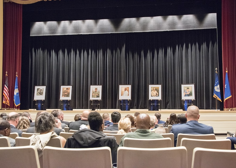 Family members of the six Fallen Heroes killed Dec. 21, 2015, by a suicide bomber near Bagram Air Field, Afghanistan, view the portraits of their departed loved ones during the unveiling ceremony May 16 at the Little Hall Auditorium, Marine Corps Base Quantico, Va. The portraits were hung later that day in the Air Force Office of Special Investigations Headquarters Hall of Heroes. (U.S. Air Force photo/Special Agent Cameron MacKenzie)