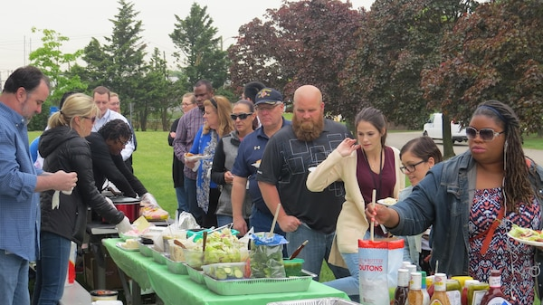 Subsistence employees enjoy a variety of food during an outdoor Spring Fling event May 11 at the Naval Support Activity Philadelphia. Employees brought their favorite pot luck meals and ate hamburgers and hot dogs.