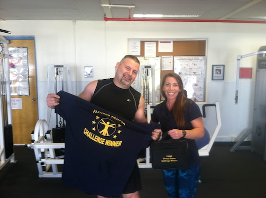Steve Edmonson, DLA Distribution San Joaquin Maintenance Division Group deputy, is announced as the winner of the Fitness Center Challenge by trainer Jessica Sanchez.