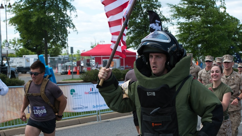 Navy Lt. Daniel Glenn runs with the American flag at the Marine Corps Historic Half Marathon in Fredericksburg, Virginia, May 15, 2016. Despite being exhausted and in pain from his 85 pound bomb suit, Glenn, with a large group of Marines at his back, charged the final leg of the course to complete the half marathon.