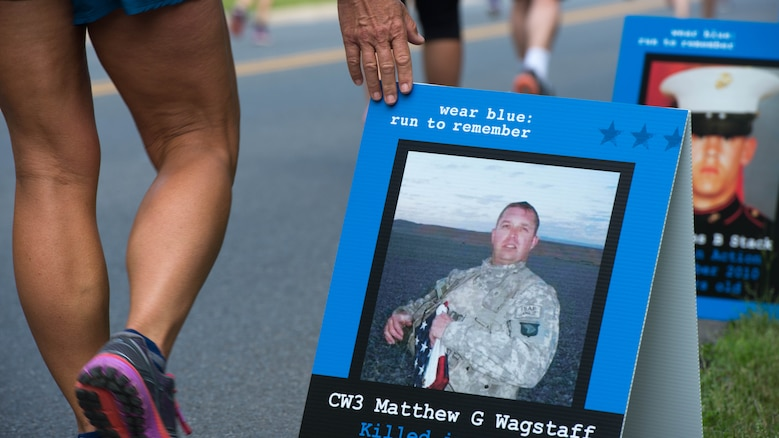 A participant walks through the Blue Mile at the Marine Corps Historic Half Marathon in Fredericksburg, Virginia, May 15, 2016. The participant paid her respects to the fallen U.S. military members by gently touching all of the dozens of signs on display.