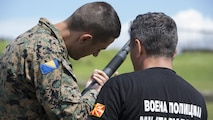Sgt. Maj. Sasha Toshevski, first sergeant and non-lethal weapons instructor with the Macedonian Special Forces Regiment, instructs a Bosnian soldier on shotgun loading techniques while training in a non-lethal weapons class, during exercise Platinum Wolf 2016 at Peacekeeping Operations Training  Center South Base in Bujanovac, Serbia, May 13, 2016. Seven countries including Bosnia, Bulgaria, Macedonia, Montenegro, Slovenia, Serbia, and the United States joined together to enhance their ability to work together and master the use on non-lethal weapons systems.