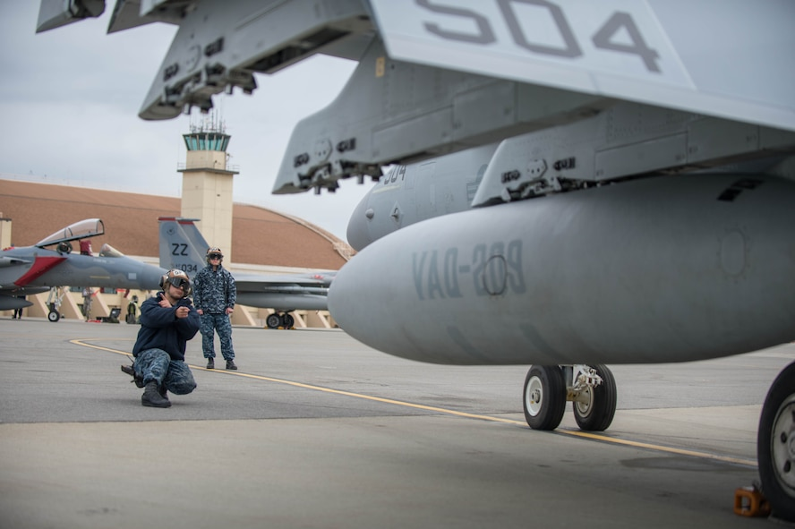 U.S. Navy Aviation Structural Mechanic 3rd Class Gabrial Rodriguez, from VAQ-137, Naval Air Station Whidbey Island, Washington, conducts pre-flight checks on an EA-18G Growler aircraft preparing for a sorties May 9, 2016 during RED-FLAG-Alaska (RF-A) 16-1 at Eielson Air Force Base, Alaska. Sorties for RF-A are flown in the Joint Pacific Alaska Range Complex, a more than 67,000 square mile area that provides a realistic training environment and allows commanders to train for full spectrum engagements, ranging from individual skills to complex, large-scale joint engagements. (U.S. Air Force photo by Staff Sgt. Shawn Nickel/Released)
