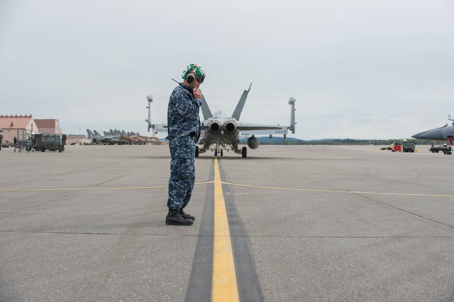 Aviation Electronic Technician Chief Christopher Fink, from VAQ-137, Naval Air Station Whidbey Island, Washington, stands in the jet wash of an EA-18G Growler aircraft after supervising the launch of two jets for a sortie May 9, 2016, during RED-FLAG-Alaska (RF-A) 16-1 at Eielson Air Force Base, Alaska. The aircraft logged more than 500 tactical flying hours during RF-A 16-1, which requires maintainers to work around the clock. (U.S. Air Force photo by Staff Sgt. Shawn Nickel/Released)