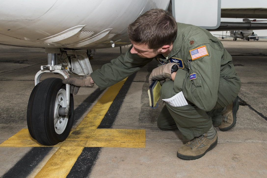 """Maj. Ryan Scott, 99th Flying Training Squadron """"A"""" flight commander and T-1A Jayhawk instructor pilot, performs pre-flight checks on a T-1A before a training mission at Joint Base San Antonio-Randolph May 16, 2016. Instructor pilot trainees who attend pilot instructor training at JBSA-Randolph combine to fly 8,500 hours a year and 80 sorties per week."""