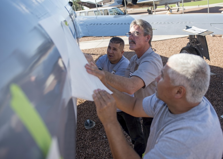 From left to right: Jesse, Mike, and Frank, M1 Support Systems aircraft corrosion specialists at Holloman Air Force Base N.M., pull of the outer sheet of a decal to an F-84F Thunderstreak at Heritage Park here May 16. These contractors sand and re-paint two aircraft inside Heritage Park each year to keep them from corroding. (Last names are being withheld do to operational requirements) (U.S. Air Force photo by Airman 1st Class Randahl J. Jenson)