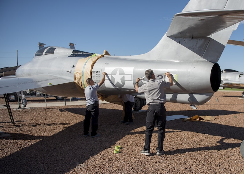 From left to right: Jesse and Mike, M1 Support Systems aircraft corrosion specialists at Holloman Air Force Base N.M., apply decals to an F-84F Thunderstreak after sanding and re-painting it at Heritage Park here May 16. The F-84F Thunderstreak was used by Strategic Air Command, Tactical Air Command, the Air National Guard and NATO Air Forces during the Korean War. (Last names are being withheld do to operational requirements) (U.S. Air Force photo by Airman 1st Class Randahl J. Jenson)