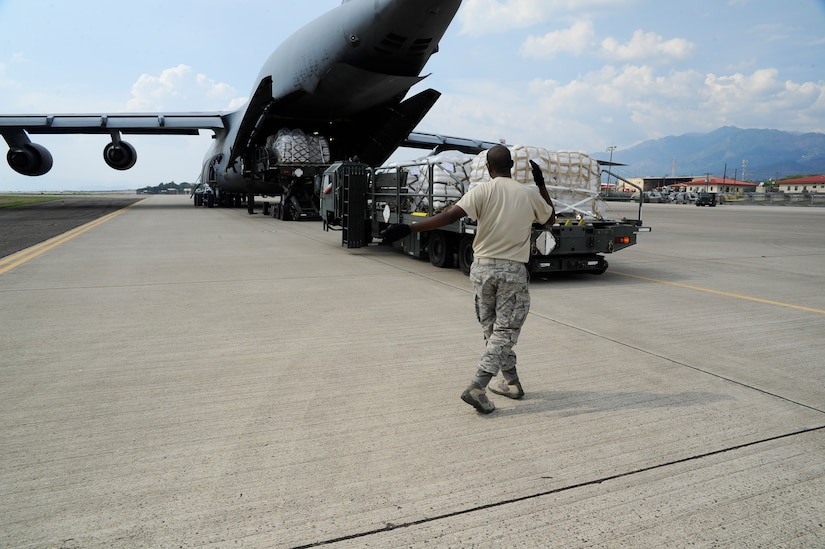 A member of the 612th Air Base Squadron marshals the driver of a K Loader at Soto Cano Air Base, Honduras, May 13, 2016. In 2015, over 142,000 pounds of cargo valued at $590,000 passed through Soto Cano AB via the Denton Program. (U.S. Army photo by Martin Chahin)