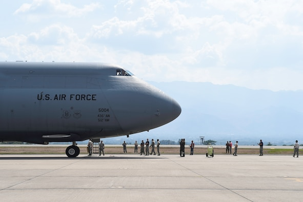 Members of the 612th Air Base Squadron prepare to board a C-5M Super Galaxy from Dover Air Force Base, Del., after its arrival to Soto Cano Air Base, Honduras, May 13, 2016. Through the Denton Program, the C-5 delivered approximately 85,000 pounds of rice and beans which is to be distributed to people in the Yoro Department of Honduras by a local non-governmental organization. (U.S. Air Force photo by Staff Sgt. Siuta B. Ika)